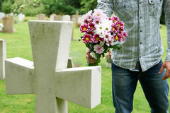 Man Laying Flowers On Grave Stock Photo