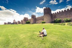 Man laying on grass with dog by city Avila,Spain.  Stock Photos