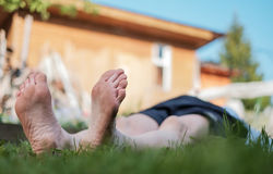 Man laying on grass field. He relax on nature in summer. Look up on sky Royalty Free Stock Photos