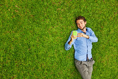 Man laying on a grass talking on a mobile phone Royalty Free Stock Image