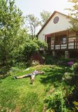 Man laying on green fresh grass in his garden near country house. Lifestyle, laisure timespending royalty free stock images