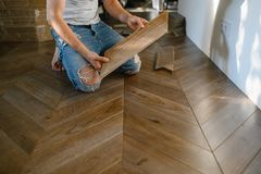 Man laying parquet flooring - closeup on male hands. worker joining parquet floor stock image