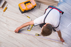 The man laying laminate flooring in construction concept. Man laying laminate flooring in construction concept royalty free stock photography