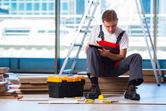 The man laying laminate flooring in construction concept Stock Image