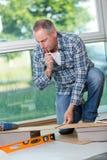 Man laying laminate flooring in home. Man laying laminate flooring in a home Royalty Free Stock Photo