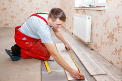 Man laying laminate flooring. Young handyman installing wooden floor in new house royalty free stock photos