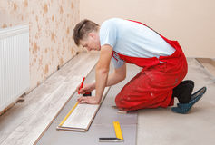 Man laying laminate flooring. Young handyman installing wooden floor in new house royalty free stock image