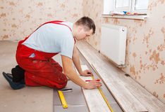 Man laying laminate flooring. Young handyman installing wooden floor in new house stock image