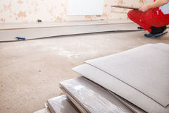 Man laying laminate flooring. Young handyman installing wooden floor in new house stock photography