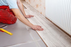 Man laying laminate flooring. Young handyman installing wooden floor in new house stock photos