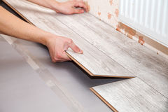 Man laying laminate flooring. Young handyman installing wooden floor in new house, hands closeup stock image