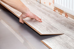 Man laying laminate flooring. Young handyman installing wooden floor in new house, hands closeup stock photos