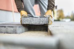 Man laying a paving brick placing it on the sand foundation. In a low angle view stock image