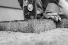 Man laying a paving stone tamping it down with a mallet Stock Photography