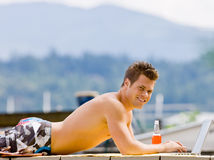 Man laying on pier on laptop Royalty Free Stock Images