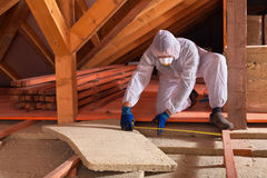 Man laying rockwool panels in the attic of a house Stock Photography