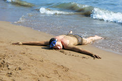 Man laying on sand. Relaxed man with underwater mask lying on a beach in shallow water Royalty Free Stock Images