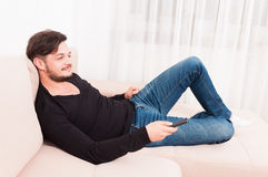 Man laying on sofa holding remote control and smiling Royalty Free Stock Image