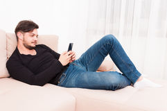 Man laying on sofa holding smartphone and texting. Young man laying on sofa holding smartphone and texting indoor with copy text space Stock Photos