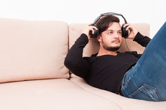 Man laying on sofa putting on headphones. Listening to music relaxing and enjoying indoor with copy text space Royalty Free Stock Image