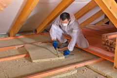 Man laying thermal insulation layer - cutting the panels. Man laying thermal insulation layer under the roof - using mineral wool panels Stock Images