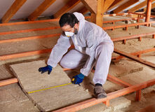 Man laying thermal insulation layer under the roof. Measuring a mineral wool panel Royalty Free Stock Photos