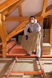 Man laying thermal insulation layer under the roof Stock Photo