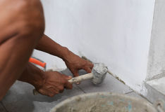 Man laying tile with rubber hammer Stock Photos