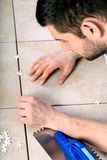 Man laying tiles. Young man laying tiles on the floor Royalty Free Stock Photos