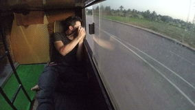 Man laying in train and photographing landscape through the window. stock footage