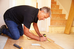 Man laying wood panel flooring during a house refurbishment Royalty Free Stock Photography