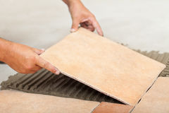 Man lays ceramic floor tiles - closeup Royalty Free Stock Images