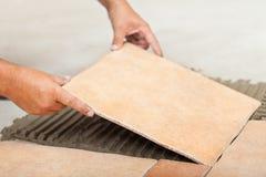 Man lays ceramic floor tiles - closeup Royalty Free Stock Images