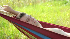 A man lays on a hammock stock footage