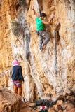 Man lead climbing on cliff, belayer watching hi Stock Photo