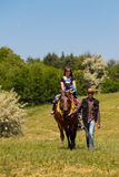 Man leading a horse with young woman and her child ride Royalty Free Stock Photography