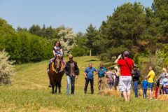 Man leading a horse with young woman and her child ride Stock Photo
