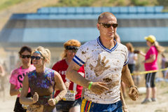 Man leading the pack at a mud race. Stock Images