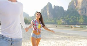 Man Leading Woman Couple Walking On Beach Holding Hands Talking Young Tourists On Vacation