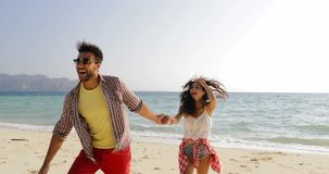 Man leading woman from water, couple holding hands walking on beach, happy smiling tourists on sea vacation. Slow motion 60 stock footage