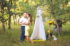 A man leads a woman with closed eyes to a picnic site with a white cloth curtain tent. Guitar and bicycle with royalty free stock image
