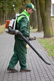 Man with leaf blower. Landscaper cleaning the runway in park using petrol leaf blower royalty free stock photo