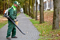 Man with leaf blower. Landscaper removing dead leaves in park using petrol leaf blower stock images