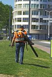 Man with leaf blower. Machine walking on grass royalty free stock photos