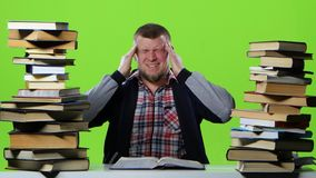 Man leafing through a textbook, it suffers from headaches. Green screen stock video
