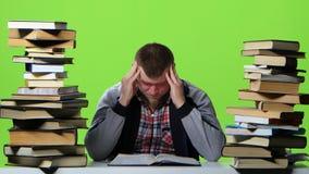 Man leafing through a textbook, it suffers from headaches. Green screen