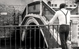 Man leaning against a balustrade. Black and white: lunch break at a bridge in Venice stock photo