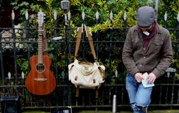 Man Leaning Against Black Steel Fence Beside White and Brown Sling Bag and Brown Acoustic Guitar Royalty Free Stock Photos