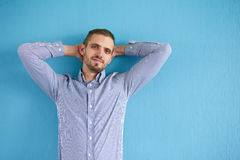 Man leaning against a blue wall Royalty Free Stock Image