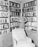 Man leaning against a bookshelf in a library Stock Images